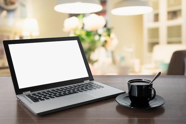 Laptop met een leeg scherm met koffie op tafelblad. thuiswerken. koffiepauze. opleiding. e-learning.
