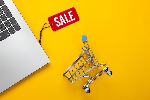Laptop met een rood verkooplabel, winkelwagentje op geel. grote uitverkoop, kortingen, online winkelen.