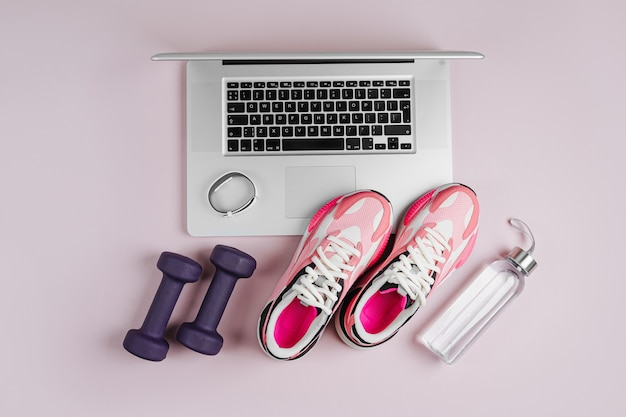 Laptop met fitness sportuitrusting en sneakers op een roze achtergrond.