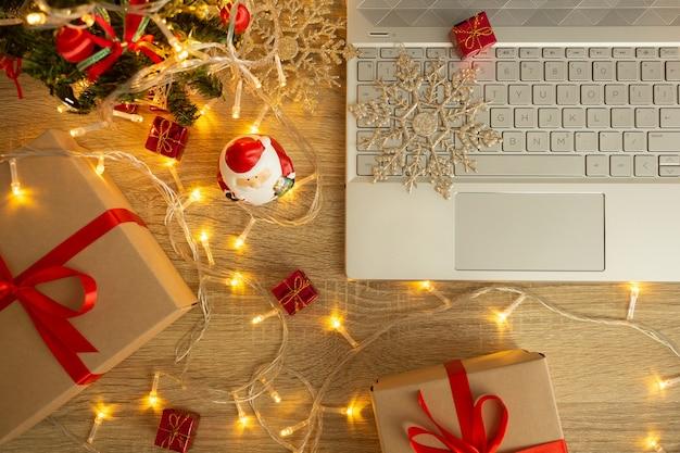Laptop met geschenkdozen en kerstversiering op houten tafel.