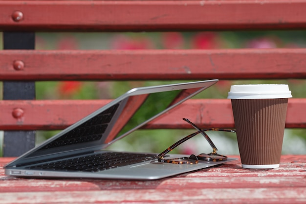 Laptop met glazen en notebook liggend op bankje in stadspark, outdoor studie of internet freelance werkconcept