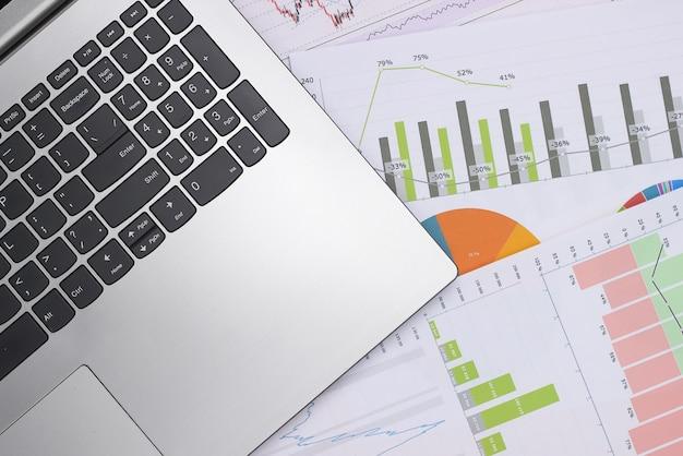 Laptop met grafieken en grafieken. businessplan, financiële analyse, statistieken. bovenaanzicht