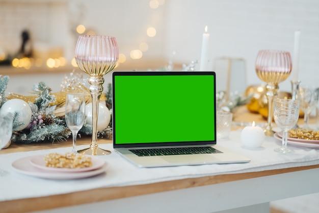 Laptop met groen scherm - chromakey in de buurt van new year's decoraties. kerstthema. sjabloon.