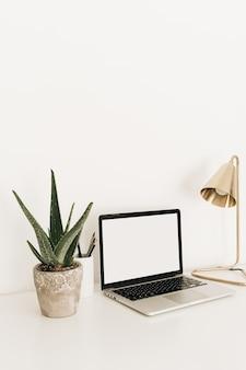 Laptop met het lege scherm van de exemplaarruimte op witte lijst met gouden lamp en huisinstallatie aloë vera