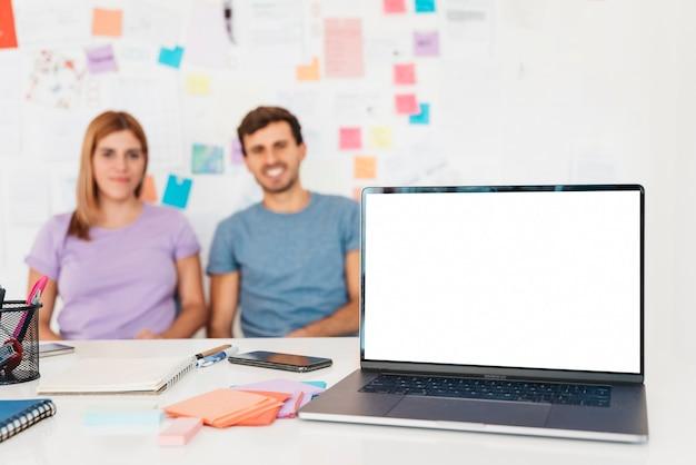 Laptop met kantoorbehoeften tegen achtergrond van paar en muur met nota's