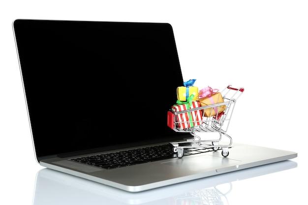 Laptop met kleine winkelwagen vol geschenken geïsoleerd op witte achtergrond