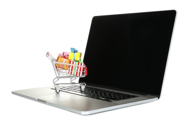 Laptop met kleine winkelwagen vol geschenken geïsoleerd