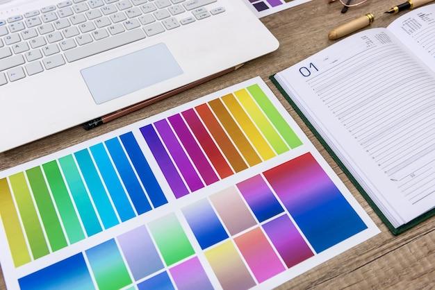 Laptop met kleurstalen op houten tafel voor huisrenovatie