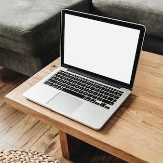 Laptop met leeg mockup-scherm op massief houten tafel.