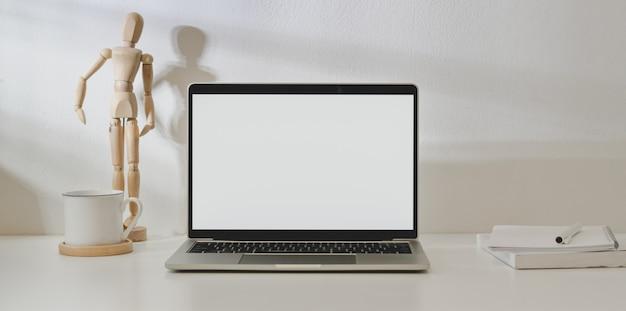 Laptop met leeg scherm computer in minimale werkplek met kantoorbenodigdheden en decoraties