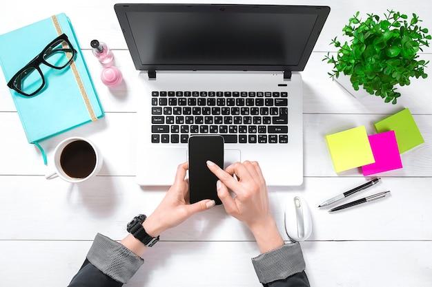 Laptop met leeg scherm en meisjeshanden. platliggende, bovenaanzicht werkruimte. ruimte kopiëren
