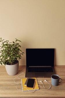 Laptop met leeg scherm, potplant, mok, geel notitieblok, pen, mobiele telefoon en koptelefoon.