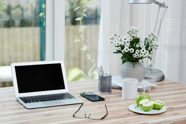 Laptop met leeg scherm, smartphone, bril en bord met groene appels voor snacks