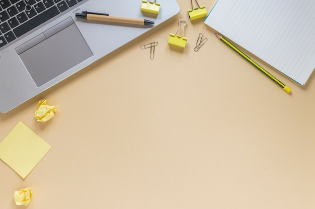 Laptop met pen; potlood; paperclips; kleverige nota's en spiraalvormige blocnote op beige achtergrond