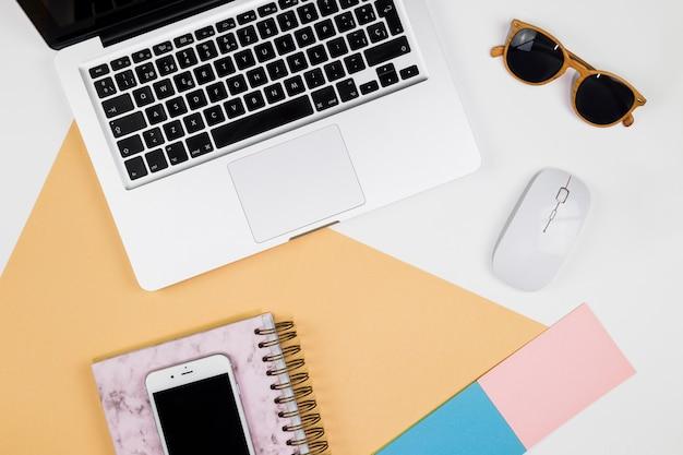 Laptop met smartphone en muis op tafel