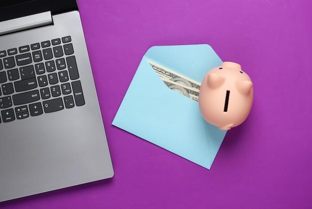 Laptop met spaarvarken, envelop met geld op paars