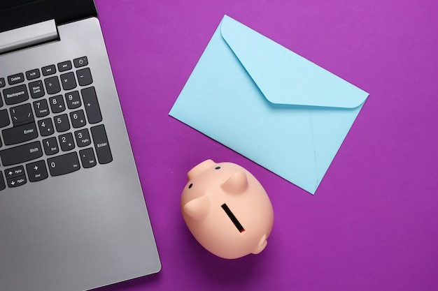 Laptop met spaarvarken, envelop op paars