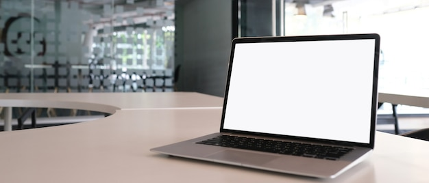 Laptop met wit scherm op witte tafel en kopieer de ruimte met kantoorachtergrond.