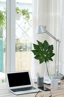 Laptop met zwart leeg scherm, kopje koffie en smartphone van tafel in thuiskantoor van persoon