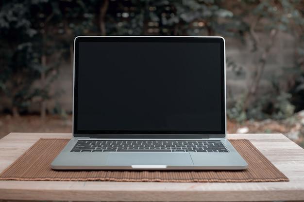 Laptop met zwart scherm op houten tafel