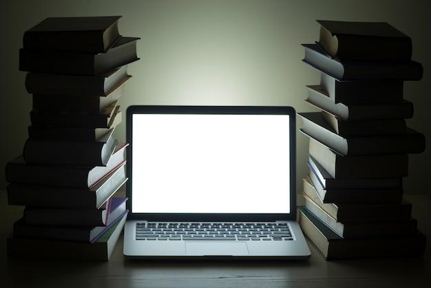 Laptop naast donkere gestapelde boeken