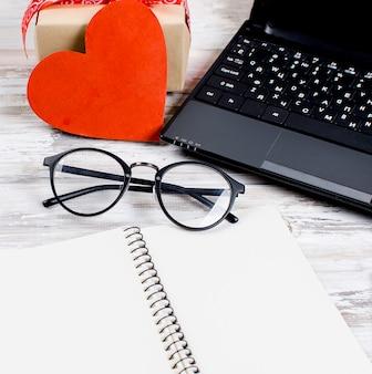 Laptop, notebook en cadeau met hart op houten tafel