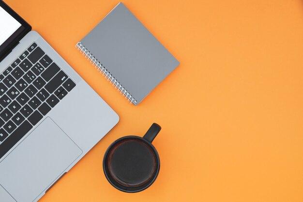 Laptop, notebook en kopje met koffie op een oranje oppervlak, bovenaanzicht, werkplek