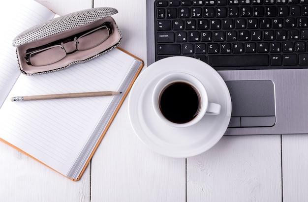 Laptop, notebook met een kopje koffie en een potlood liggend op een houten tafel. bovenaanzicht