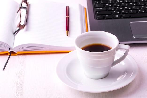 Laptop, notebook met een kopje koffie en een potlood liggend op een houten tafel