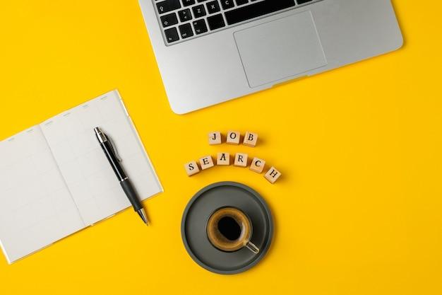 Laptop, notitieblok, pen, koffiebeker, smartphone op felgeel