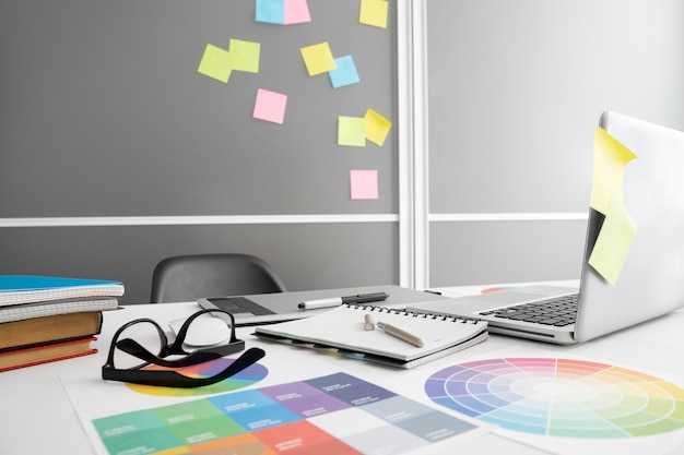 Laptop op bureau met notitieboekje en stoel