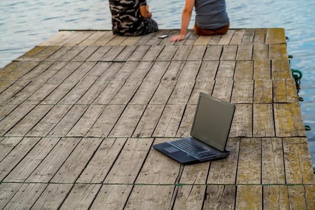 Laptop op de pier. man aan het werk op de pier.
