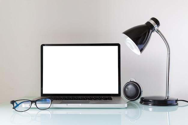 Laptop op een bureau met lamp en glazen voor thuiswerk