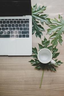 Laptop op een houten tafel en een kopje koffie