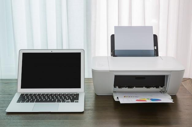 Laptop op een houten tafel met een printer