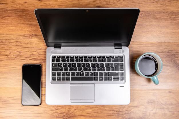 Laptop op een tafel met een kopje koffie en een mobiele telefoon van een smartphone