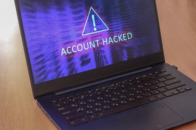 Laptop op tafel en op een blauw scherm is het tekstaccount gehackt. driehoekig waarschuwingsbord met uitroeptekensymbool. horizontaal.