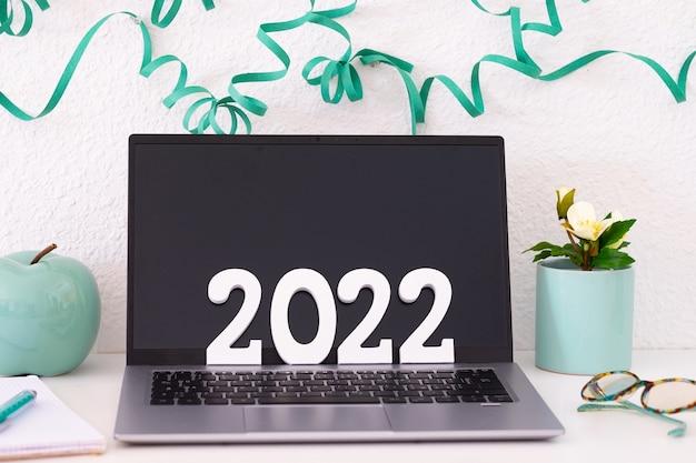 Laptop op witte achtergrond met feestelijke decoratie, met nummer 2022 in houten figuren. zwart scherm. werken, werken op afstand, gelukkig nieuwjaar op het bureau