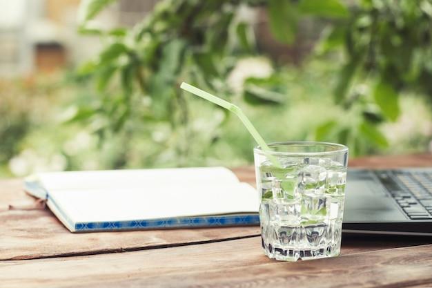 Laptop, open dagboek en een glas met een verfrissend koud drankje met ijsblokjes en muntblaadjes op een houten tafel. het concept van werk in de natuur, freelancen, werk op vakantie