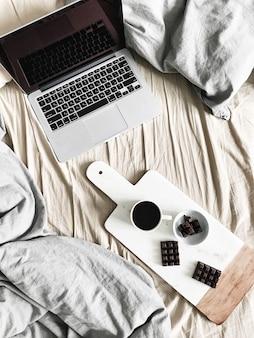 Laptop, pastelkleurig linnengoed, ontbijt met koffie en chocolade op marmeren snijplank. plat lag, bovenaanzicht levensstijl concept.