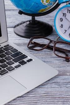 Laptop pc met bril en klok op een houten tafel. reizen en leren concept. zakelijk en reizen.