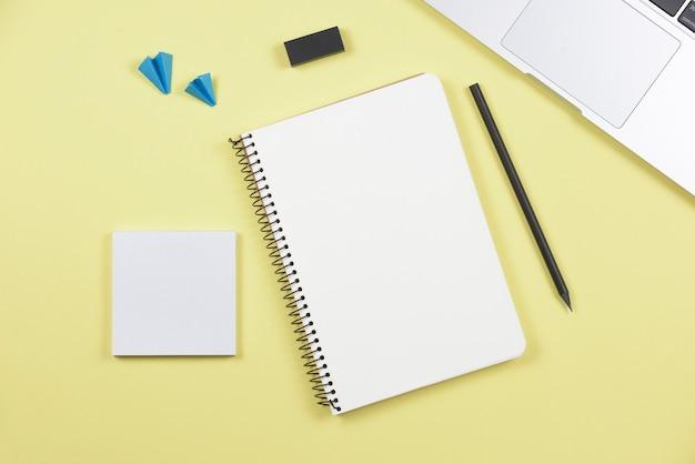 Laptop; potlood; spiraal notitieboekje; zelfklevend notitieblok; vliegtuig en gum op gele achtergrond