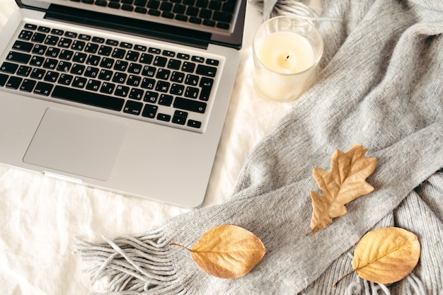 Laptop, sjaal, gele herfstbladeren, kaars op wit bed. werk thuis concept. herfst, herfst, winter samenstelling. plat lag, bovenaanzicht.