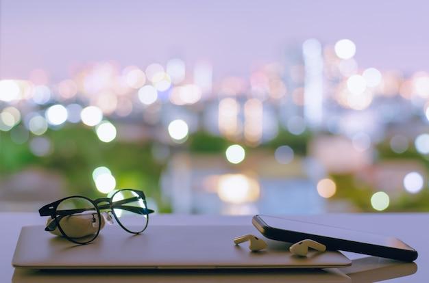 Laptop, smartphone en oortelefoon worden uitgezet op tafel met kleurrijke stads bokeh lichten.