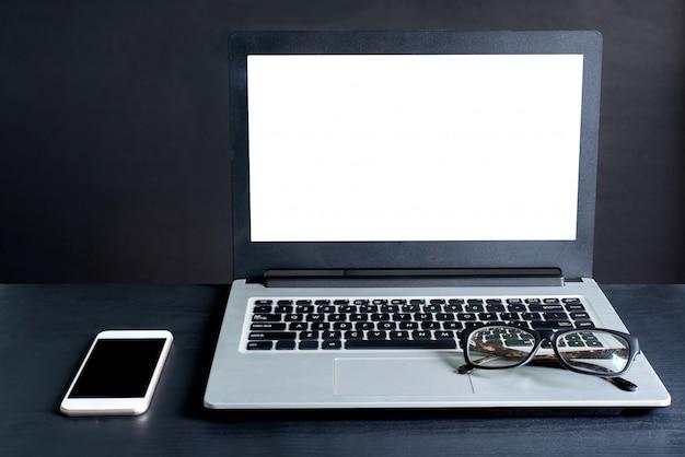 Laptop, smartphone, glazen, op zwarte houten tafel met zwarte achtergrond