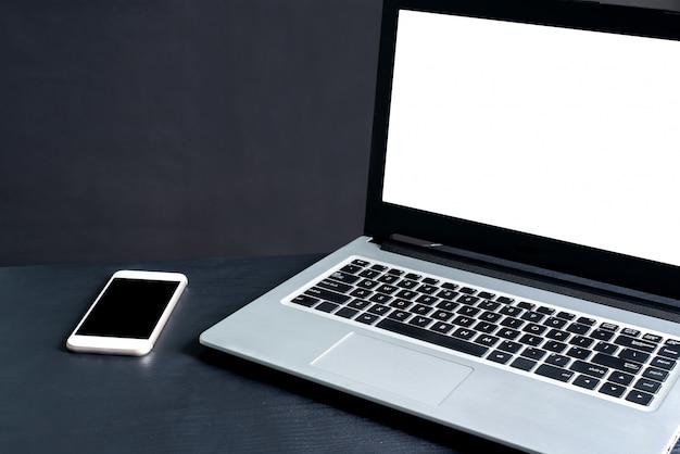 Laptop, smartphone, op zwarte houten tafel met zwarte achtergrond