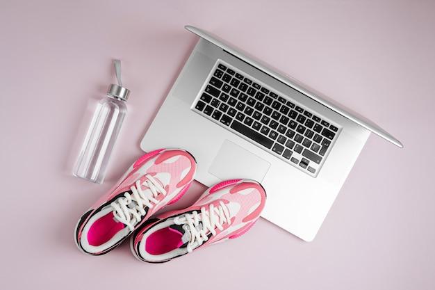 Laptop, sneakers en waterfles op een roze achtergrond. online fitnessprogramma. thuis trainen.