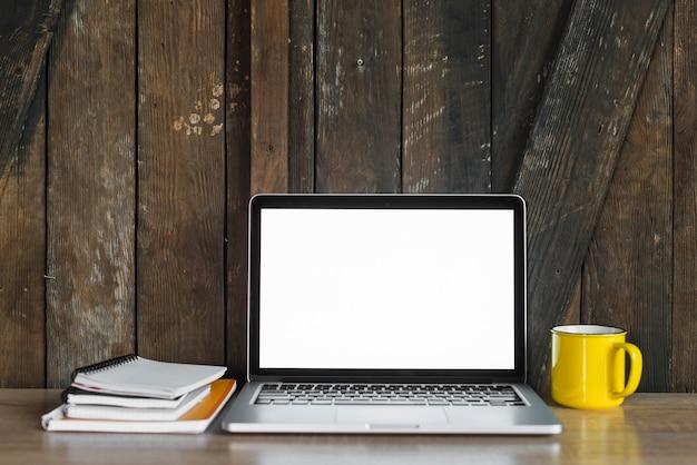 Laptop; spiraal kladblok en koffie tegen houten muur