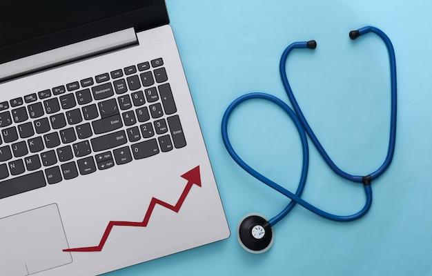 Laptop, stethoscoop met groeipijl op blauw