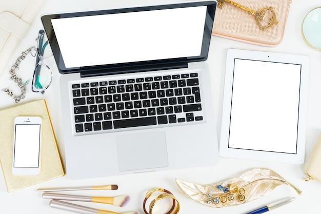Laptop, tablet en telefoon met gouden vrouwenaccessoires bespotten een platliggende gestileerde scène